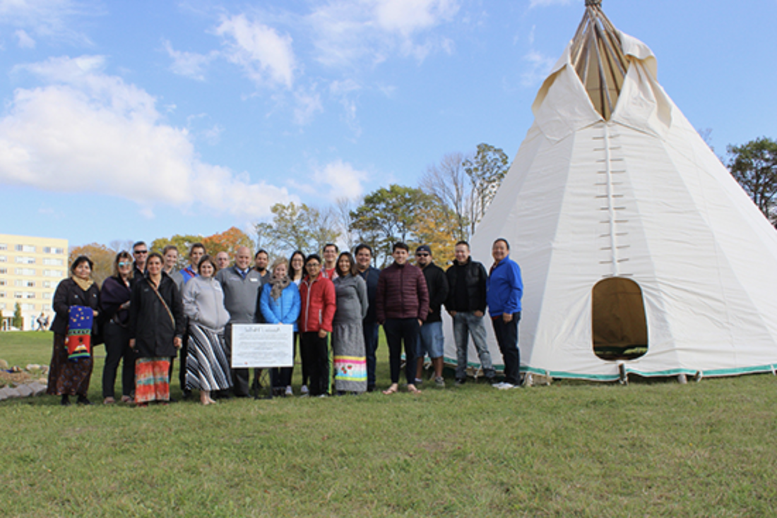group of people standing beside Lakehead tipi