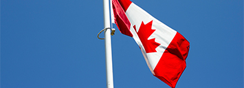 The Canadian flag blowing in the wind on a beautiful clear day